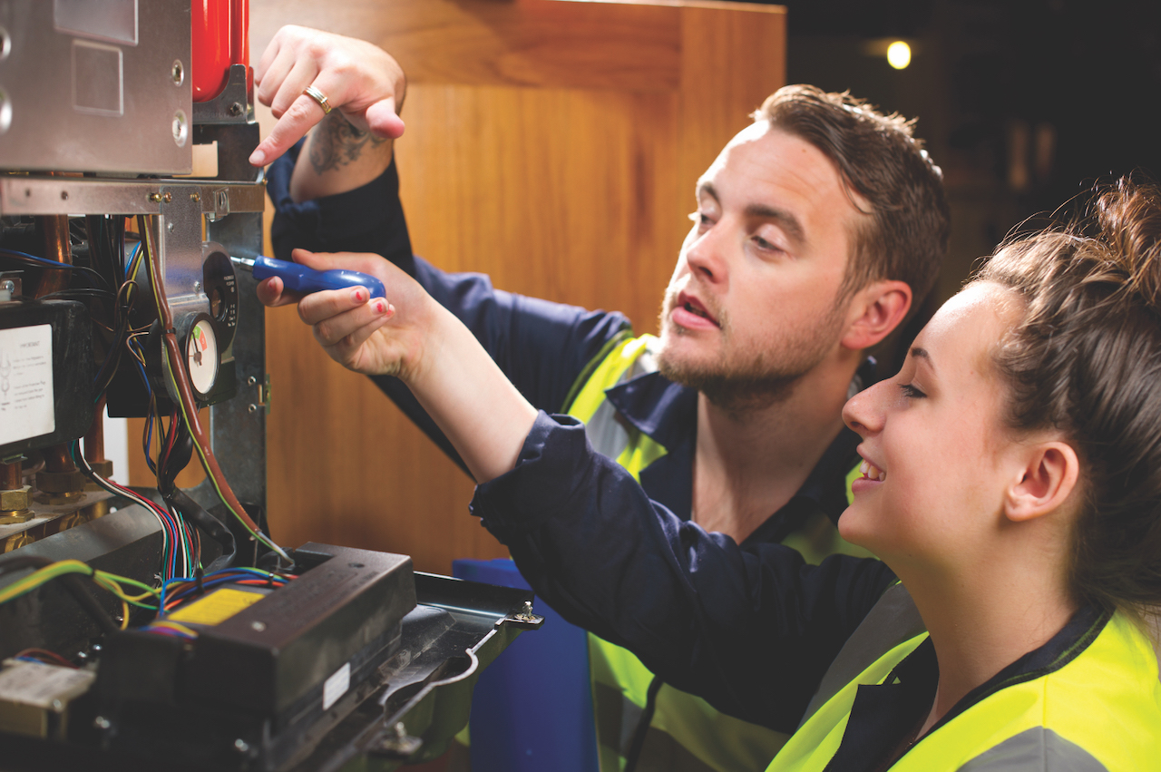 young female plumber apprentice at work with her boss